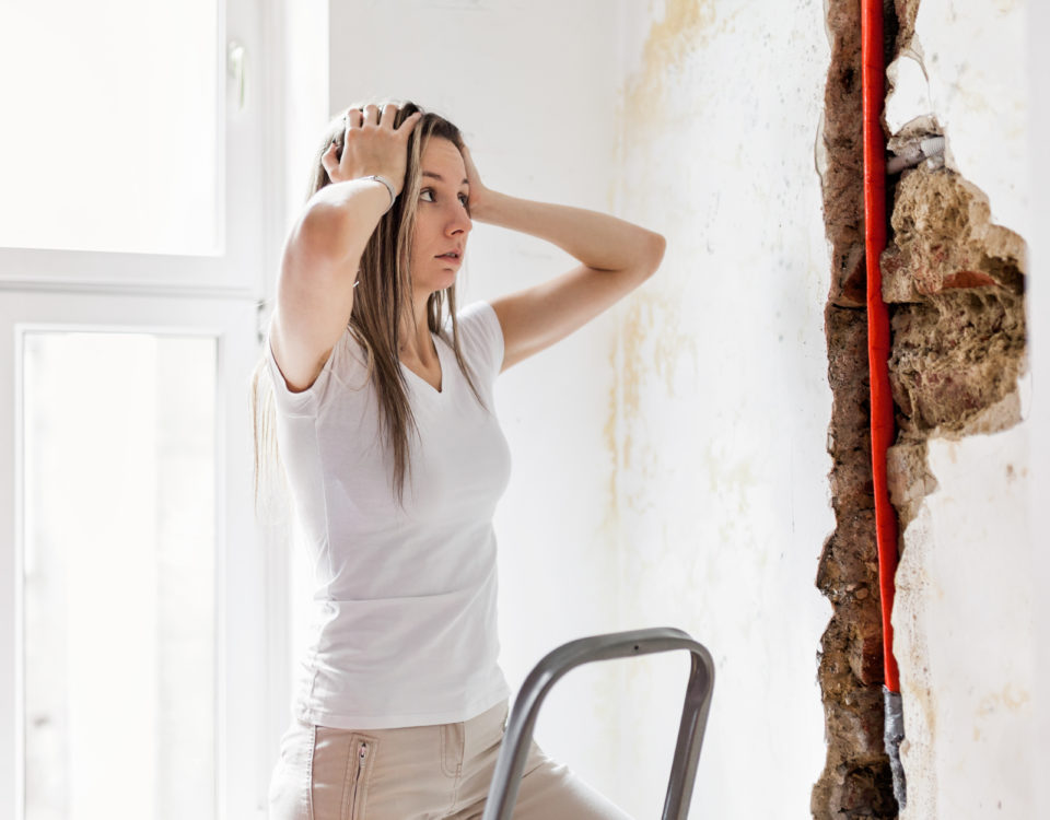 Woman looking at damage after a slow leak leak