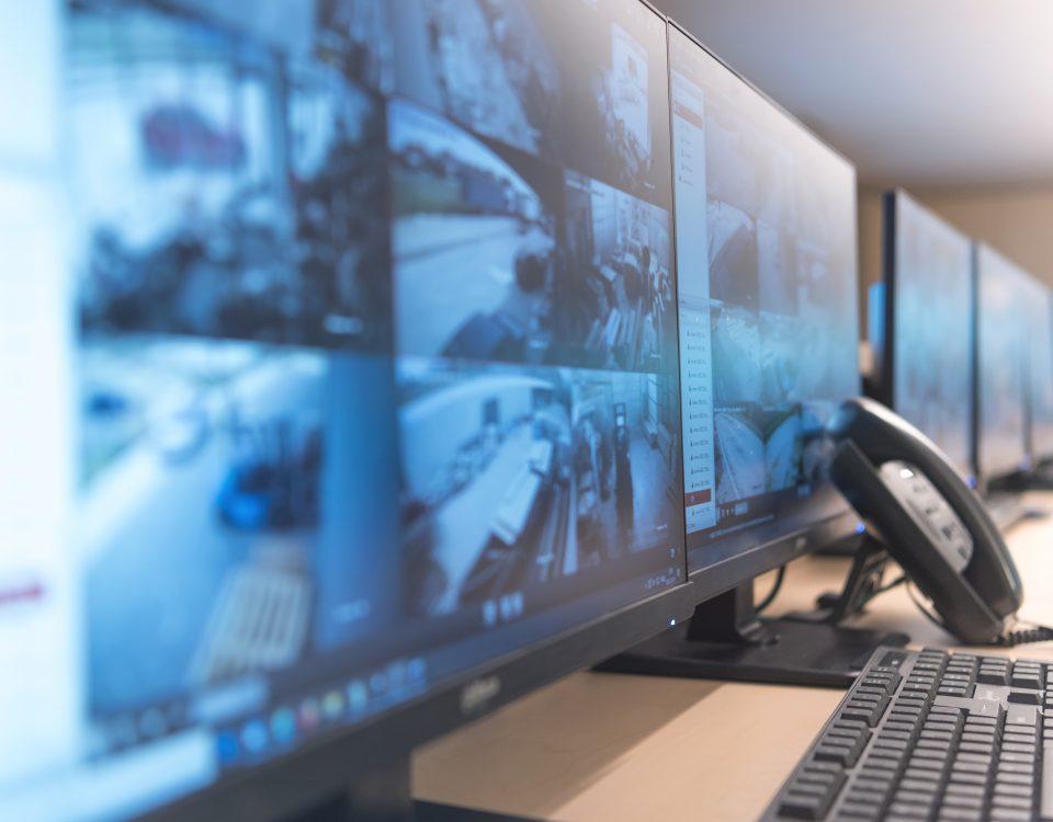 Security guard monitoring modern CCTV cameras in surveillance room.
