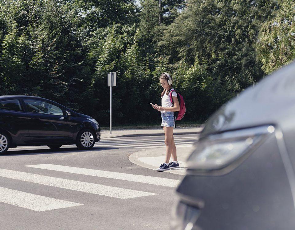 Schoolgirl with headphones and mobile phone on pedestrian crossing